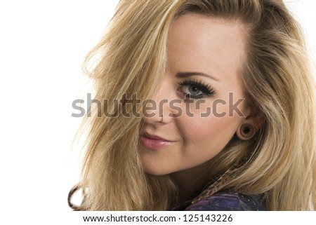 Beautiful blonde woman smiling with hair covering one eye - stock photo