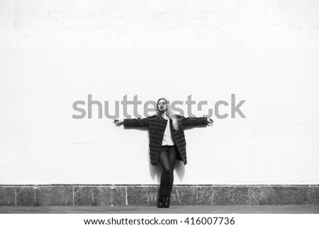 Beautiful blonde woman standing by a stone wall - stock photo