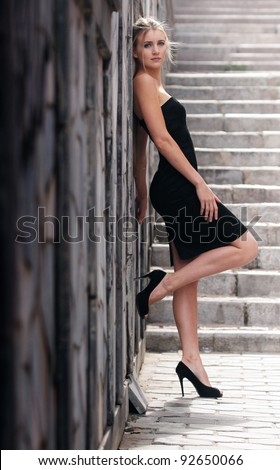 Beautiful blonde woman standing by a stone wall against the staircase on a summer day - stock photo