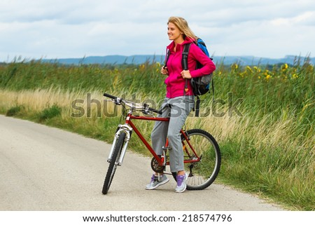 Beautiful blonde woman standing on the country road with her bike and enjoy in view,Woman with a bike