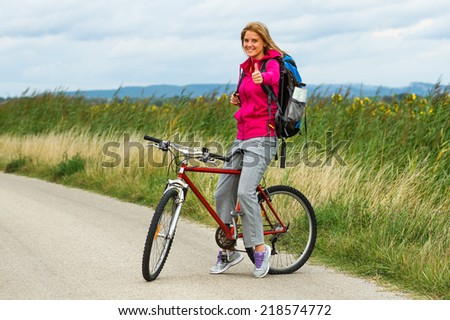 Beautiful blonde woman standing on the country road with her bike and showing thumbs up,Thumbs up for cycling!