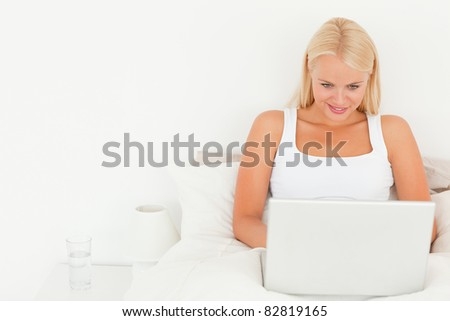 Beautiful blonde woman using a laptop in her bedroom - stock photo