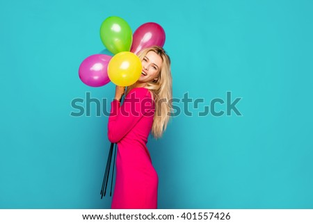 beautiful blonde woman very energetic, smiling and holding some colored balloons on blue background