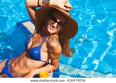 Beautiful blonde woman wearing a hat and sunglasses, enjoying the pool, summer time