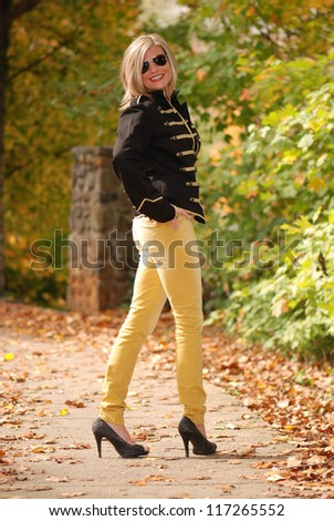 Beautiful Blonde Woman Wearing a Jacket, Gold Jeans and heels - stock photo