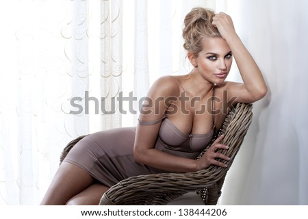 Beautiful blonde woman wearing fashionable lingerie, sitting on wicker chair in bright room. - stock photo