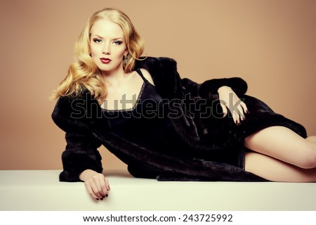 Beautiful blonde woman wearing mink fur coat. Fashion, beauty. Luxurious lifestyle. Studio shot. - stock photo