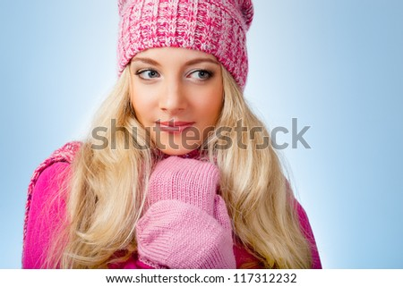 beautiful blonde woman wearing pink knitwear over blue background looking to the side - stock photo