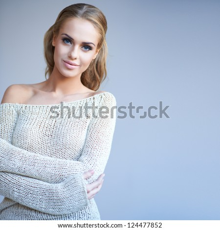 Beautiful blonde woman with a gentle smile looking serenely at the camera, half body studio portrait - stock photo