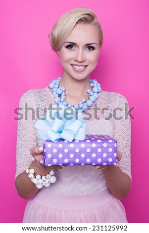 Beautiful blonde woman with cream dress giving colorful gift. Christmas. Holiday. Studio portrait over pink background  - stock photo