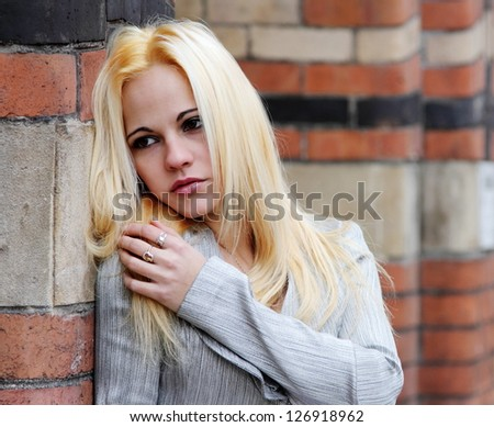 Beautiful blonde woman with long golden hair leaning against colored wall - stock photo
