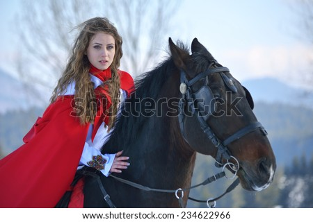 Beautiful blonde woman with red cloak with horse outdoor in winter season - stock photo