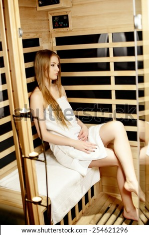 beautiful blonde woman wrapped in a towel resting in the sauna - stock photo