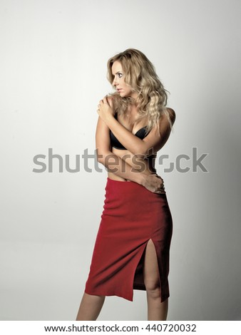 Beautiful blonde women looking right and touch her body. She is posing in studio on white background. - stock photo