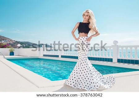 Beautiful blonde young slim woman model girl standing next to an exclusive pool and spa Willas in a long wedding dress carnival ballroom polka-dots in the island of Santorini island spain - stock photo