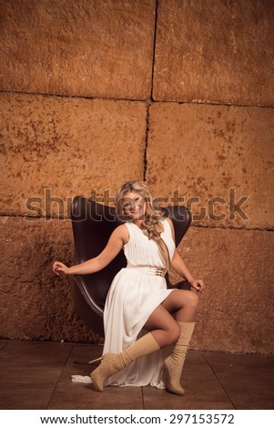 Beautiful blonde young woman in a long dress in a luxurious interior expensive - stock photo
