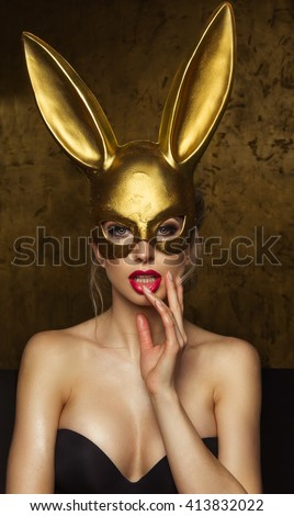 Beautiful blonde young woman in carnival  gold rabbit mask with long ears  - stock photo