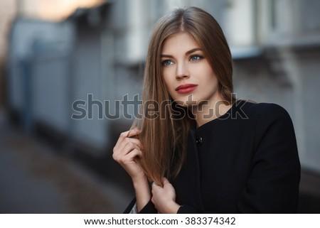Beautiful blonde young woman in nice black coat. Posing on urban background. Fashion Photo - stock photo