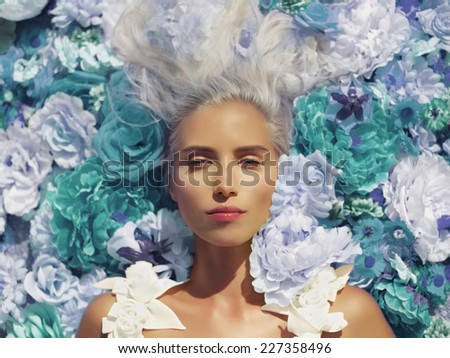 Beautiful blonde young woman lying in flowers - stock photo