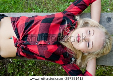 beautiful blonde young woman sleeping relaxed on a bench in a park or on the woods - stock photo