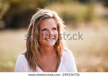 Beautiful Blonde Young Woman Smiling away from camera natural laughter - stock photo