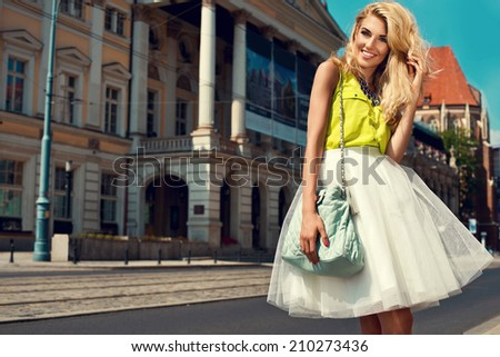 Beautiful blonde young woman wearing fashionable clothes and walking on the street  - stock photo