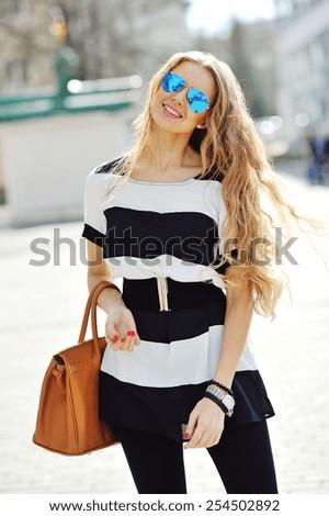 Beautiful blonde young woman wearing sunglasses - stock photo