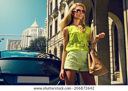 Beautiful blonde young woman wearing sunglasses, shorts, green top and handbag walking on the street - stock photo