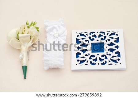 Beautiful blue and white wedding invitations and boutonniere lying at the light table in a row on celebration background copyspace closeup, horizontal picture - stock photo