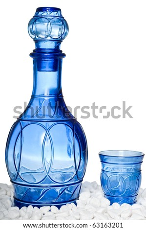 Beautiful blue bottle and tumbler on white stones, isolated on a white background