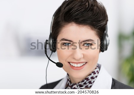Beautiful blue eyed elegant businesswoman wearing a neck scarf and headset looking at the camera with a friendly smile, head portrait - stock photo