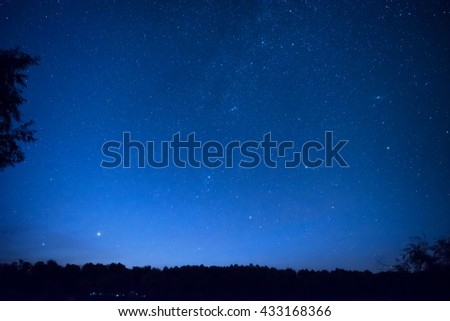Beautiful blue night sky with many stars above the forest. Milky way space background - stock photo