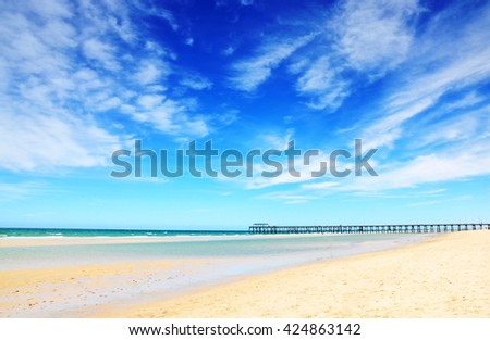 Beautiful blue sky over wide sandy beach with jetty pier in background. Taken at Henley Beach, South Australia. - stock photo