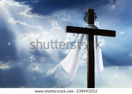 Beautiful blue sky with clouds and sunbeams shining on a cross for Easter morning. The cross includes burial cloth and crown of thorns. - stock photo