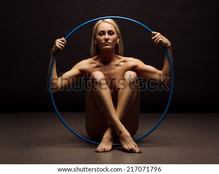 Beautiful body of young woman over dark background holding hoop - stock photo