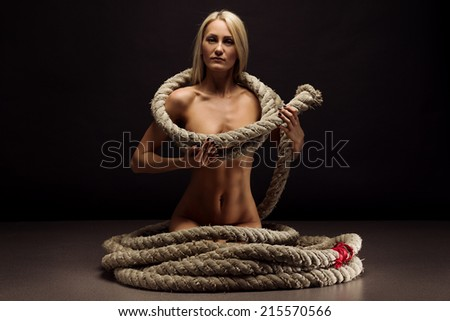 Beautiful body of young woman with a rope over dark background - stock photo