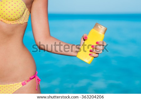 Beautiful body young woman in pink heart patterned yellow bikini and pink nails holding yellow bottled sunscreen with azure blue ocean sea beach background - stock photo