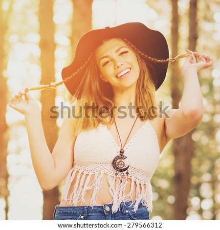 Beautiful bohemian young blonde Caucasian woman with two braids in white crochet fringe top and fedora hat smiling. Boho girl in forest on sunny summer day. Square format, retouched, vibrant colors. - stock photo