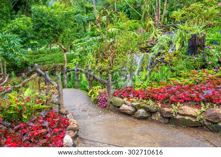 beautiful botanical garden with bridge and waterfall - stock photo