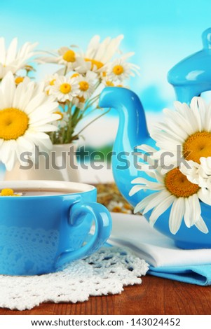 Beautiful bouquet chamomiles in teapot on wooden table on natural background
