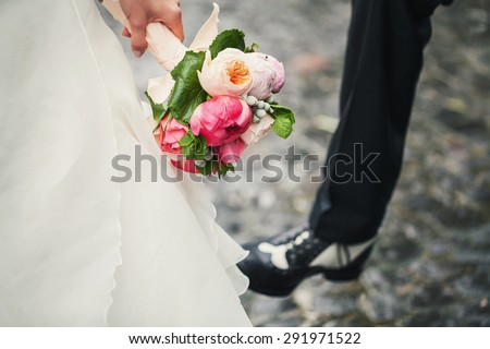 Beautiful bouquet in hands of the bride in a white dress and the groom is seen shoe