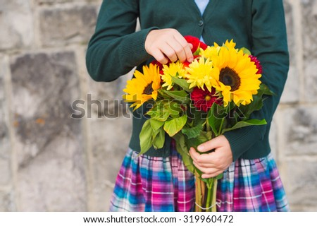 Beautiful bouquet of bright and colorful flowers holding by child's hands - stock photo