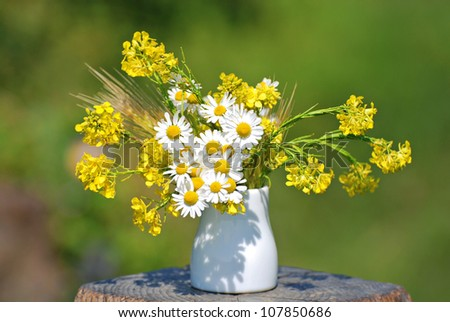 Beautiful bouquet of bright chamomiles in the white ceramic vase