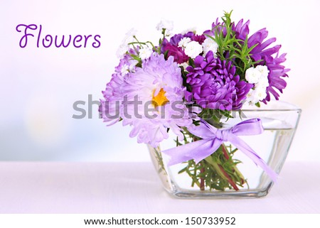 Beautiful bouquet of bright flowers in glass vase on bright background