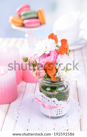 Beautiful bouquet of bright flowers in jar on table on light background
