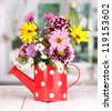 beautiful bouquet of bright flowers in watering can on wooden table - stock photo