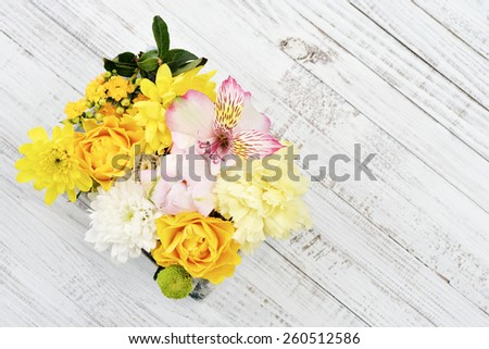 Beautiful bouquet of bright flowers on wooden background. Top view - stock photo