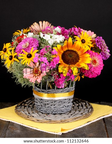 Beautiful bouquet of bright flowers on  wooden table on black background