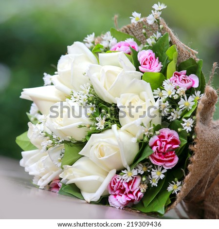 beautiful bouquet of bright white rose flowers, on table with green background
