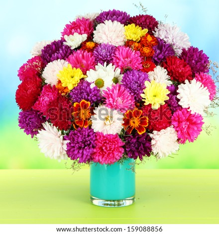 Beautiful bouquet of chrysanthemums on table on bright background - stock photo